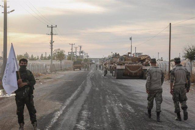 Soldados y vehículos militares de Turquía en una zona de estacionamiento para el Ejército y los rebeldes a los que apoya Ankara en Siria cerca de la frontera con el país árabe