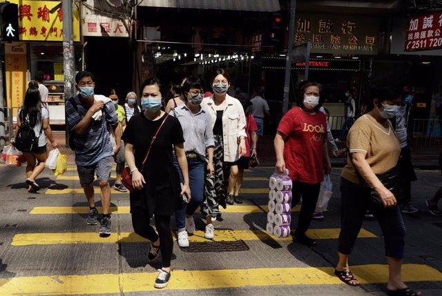 Varias personas caminan ataviadas con mascarillas por una calle de Hong Kong.