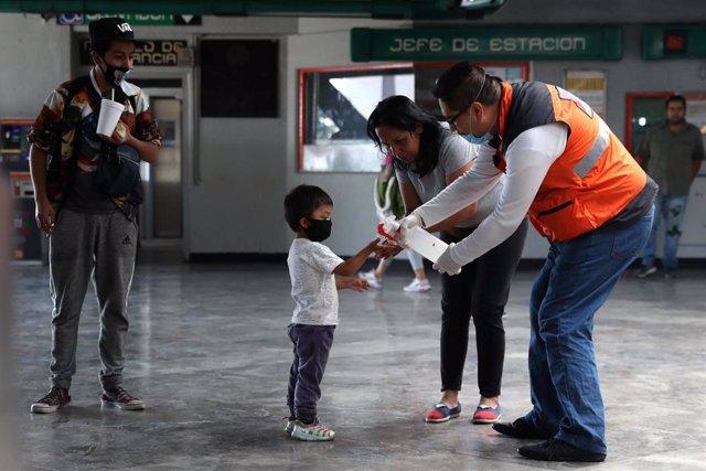 Un trabajador sanitario reparte gel desinfectante a la entrada del metro de Ciudad de México.