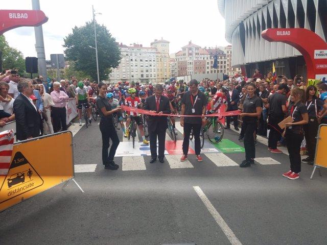 El alcalde de Bilbao, Juan Mari Aburto, corta la cinta para dar inicio a la decimotercera etapa de la Vuelta desde los alrededores del estadio San Mamés