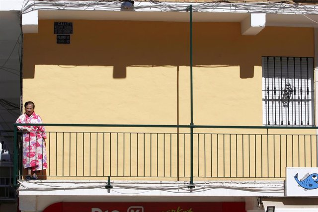 Una señora asomada a su balcón durante el periodo de confinamiento por la pandemia del COVID-19 en Málaga capital