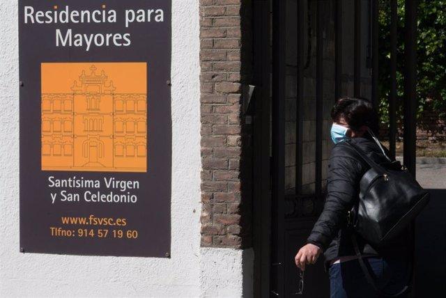 Una trabajadora protegida con mascarilla entra por la puerta de la Residencia Santísima Virgen y San Celedonio