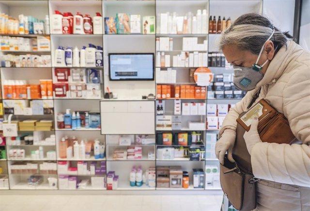 Una mujer acude a una farmacia para recoger una mascarilla durante el reparto de mascarillas gratuitas contra el Covid-19 a mayores de 65 años y colectivos de riesgo.