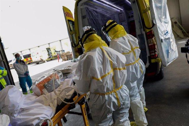Sanitarios del SUMMA protegidos con un traje protector frente al Covid-19 trasladan a un paciente desde la UVI de IFEMA al interior de la unidad móvil para su posterior traslado al Hospital Puerta de Hierro.