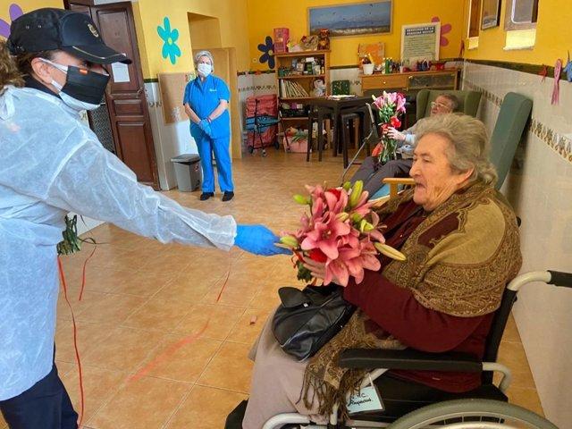 Una agente de la Policía Nacional entrega flores a una persona mayor en una residencia de Tarifa