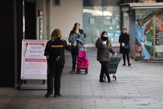 Una trabajadora de seguridad da indicaciones a las personas que esperan para entrar a uno de los supermercados de la capital durante la Semana Santa, en la que es ya la cuarta semana de confinamiento por la crisis del coronavirus en España, en Madrid, (Es