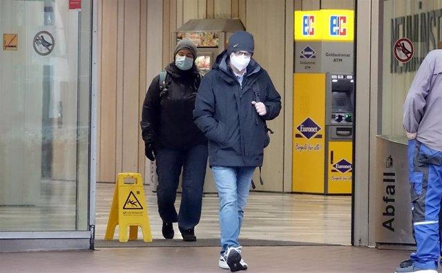 Ciudadanos con mascarilla saliendo de una estación en Neumuenster