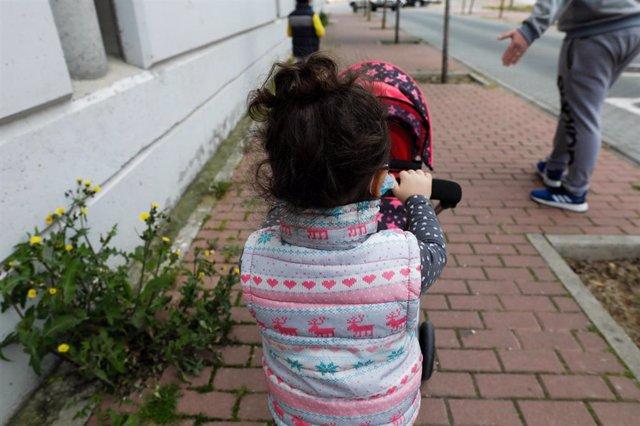 Una niña pasea por la calle empujando un carrito con un bebé de juguete junto a su padre y su hermano.