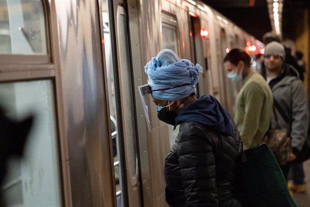 Una mujer con mascarilla y pantalla protectora en el metro de Nueva York