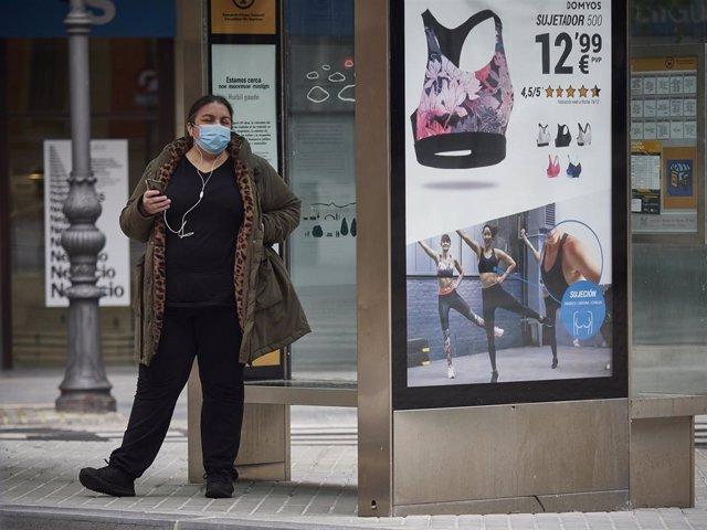 Una mujer con mascarilla espera el autobús en una marquesina en el día 47 del estado de alarma, en Pamplona / Navarra (España), a 30 de abril de 2020.