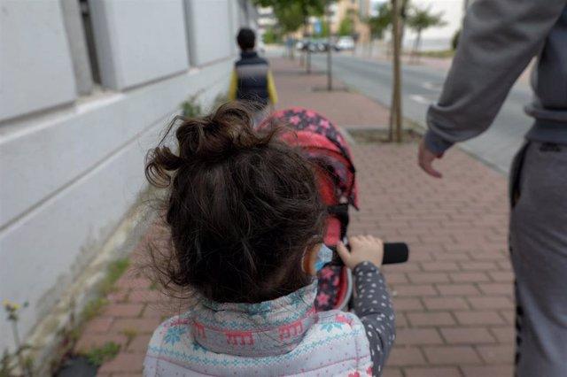 Dos niños pasean por la calle junto a su padre durante el segundo día de desconfinamiento. En Madrid (España) a 27 de abril de 2020.