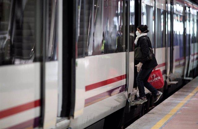 Viajeros entran en un tren de Cercanías de Atocha portando mascarilla