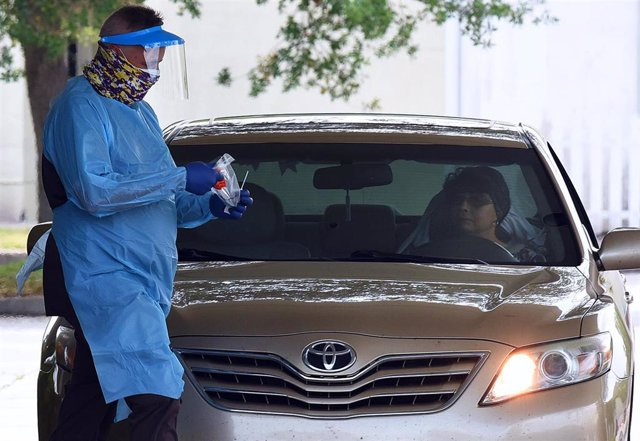 April 8, 2020 - Melbourne, Florida, United States - A healthcare worker wearing personal protection equipment prepares to administer a coronavirus test to a woman in a car on the second day of a drive-thru COVID-19 test collection facility operated by Omn
