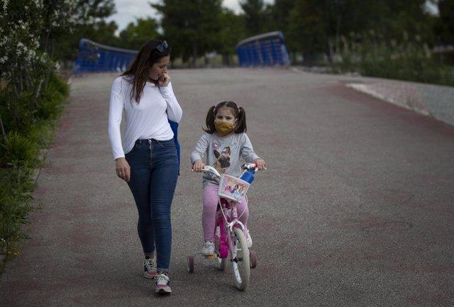 Una mujer con su hija protegida con mascarilla pasean por el parque en el tercer día de desconfinamiento de niños y preadolescentes durante el estado de alarma por la crisis del coronavirus