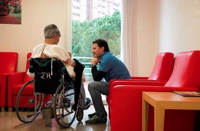 Un voluntari, parla amb un ancià, en una imatge d'arxiu