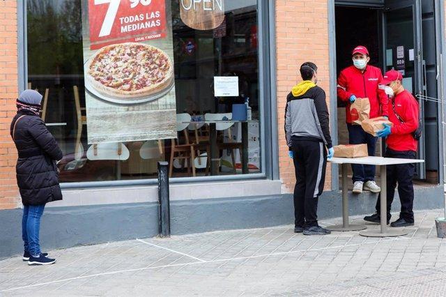 Un hombre protegido con una mascarilla recoge un menú infantil de Telepizza en el barrio de San Fermín en el distrito de Usera, cadena que, junto a Rodilla, reparte un menú escolar a más de 11.500 alumnos beneficiarios de beca comedor.