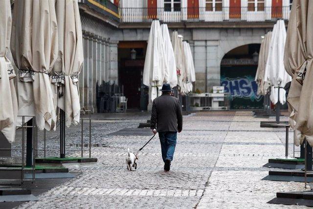 Un hombre pasea a su perro por la vac'a Plaza Mayor de Madrid durante el sexto d'a del estado de alarma por coronavirus, en Madrid (Espa–a) a 21 de marzo de 2020.
