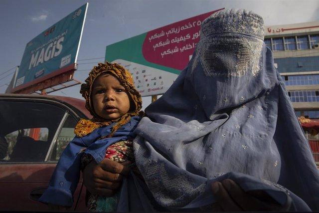 Una muje con burka con un niño en Afganistán