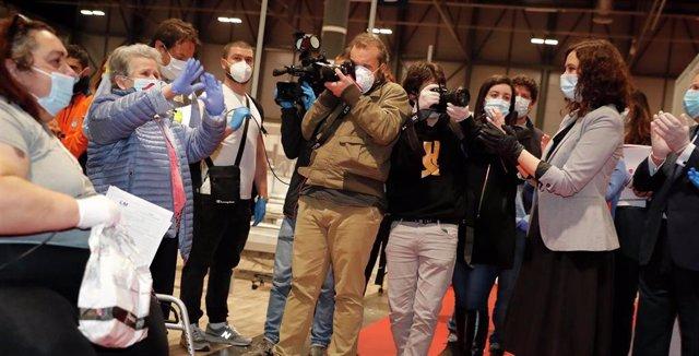 Patrocinio, con guantes y las manos en alto, la última paciente del hospital de Ifema, aplauida por la presidente de la Comunidad de Madrid, Isabel Díaz Ayuso