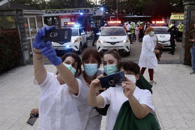 Varias sanitarias con mascarilla se hacen un selfie tras el aplauso en el Hospital Donostia junto a trabajadores de Bomberos, Ertzaintza, Guardia Municipal, Dbus, Cruz Roja, DYA, Consejo Sanitario de Osakidetza, ambulancias, y Correos, entre otros, en un