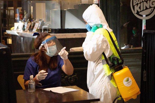 Imagen de dos trabajadores en Argentina en la pandemia del coronavirus.