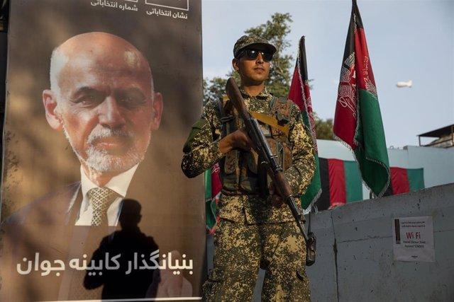 Militar afgano frente a un cartel de Ashraf Ghani