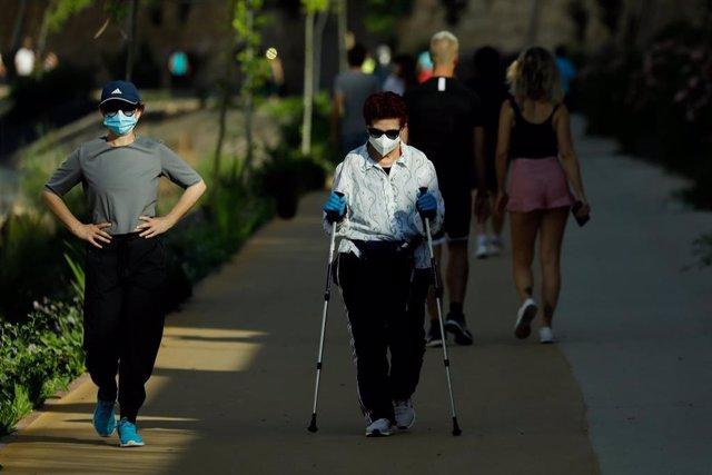 Varios adultos pasean y hacen ejercicio con mascarillas junto al río Segura, en Murcia (España), a 2 de mayo de 2020.