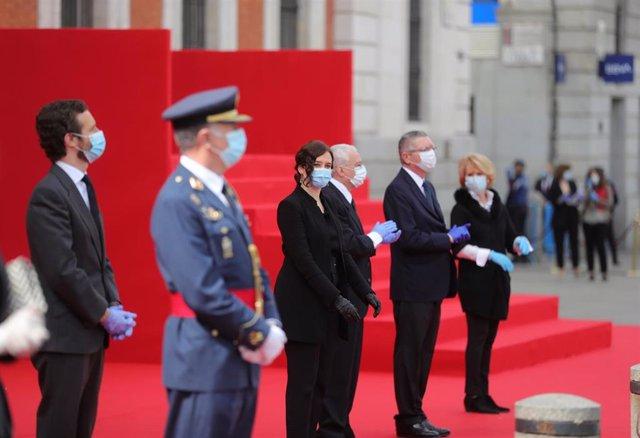 La presidenta regional, Isabel Díaz Ayuso (c), preside hoy sábado en la madrileña Puerta del Sol, las celebraciones de la fiesta de la Comunidad de Madrid, donde se homenajea este Dos de Mayo a los héroes que han luchado contra el COVID-19, en Madrid (Esp