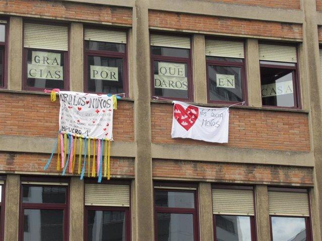 Carteles de niños hospitalizados animando a la población a quedarse en casa colgados en las ventanas de un hospital bilbaíno