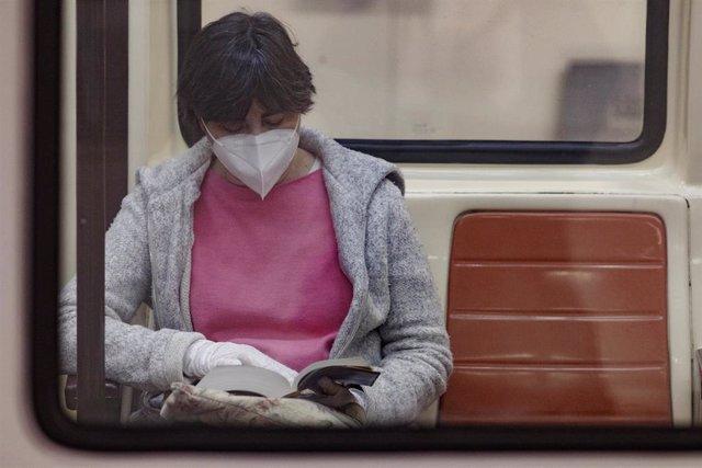 Una pasajera con una mascarilla lee en un vagón del metro un día después de que Metro de Madrid haya registrado un descenso de viajeros del 81 por ciento en hora punta por la crisis del coronavirus, en Madrid (España) a 23 de abril de 2020.