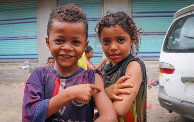 Imagen de dos niños después de recubir una vacuna.
