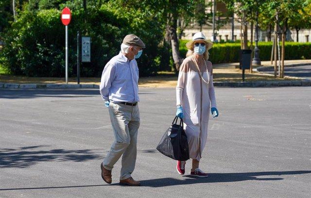 Personas mayor protegido con mascarilla pasea por el Parque de Maria Luisa, en el día en que el Gobierno permite salir a hacer deporte de forma individual y pasear con otra persona con la que se conviva, en Sevilla (Andalucía, España) a 2 de mayo de 2020.