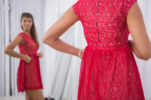 Smiling woman trying on a red dress