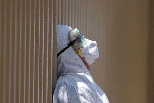 Un sanitario con traje de protección y gesto de hastío por el coronavirus