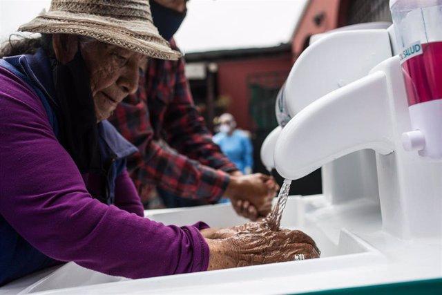 Mujer lavándose las manos en Lima, Perú