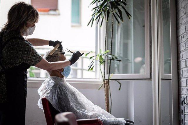 Un hombre se corta el pelo en una peluquería en el día en que estos locales pueden atender con cita previa y con limitación de aforo dentro de la primera fase de desescalada, en Vitoria / Álava / País Vasco (España), a 2 de mayo de 2020.
