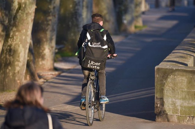 March 25, 2020 - Paris, France: A man on a bicycle doing food delivery for Uber Eats, rides on the quay of the Seine river, during the lockdown against the spread of coronavirus. (Mehdi Chebil/Contacto)