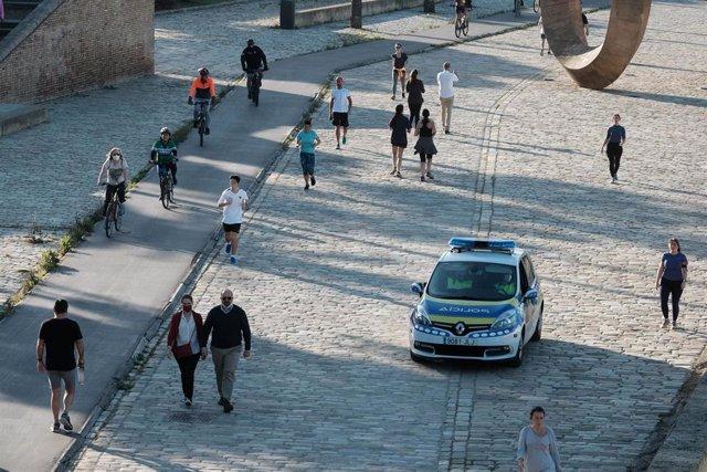 Agentes de la policía local vigilan en Sevilla el cumplimiento de las normas en el primer fin de semana para hacer deporte