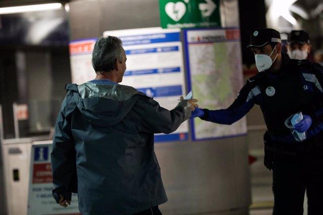 Agentes de la Policía Municipal de Madrid reparten mascarillas a los viajeros en la estación de metro de Sol