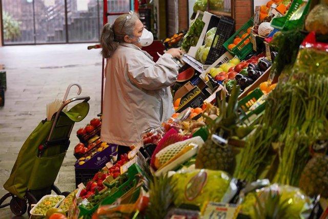 Una señora con mascarilla comprando en el mercado de Triana (Sevilla) en el tercer día de alarma. Sevilla a 17 de marzo del 2020