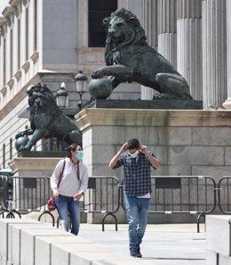 Una pareja con mascarillas pasa por delante de la fachada del Congreso de los Diputados.