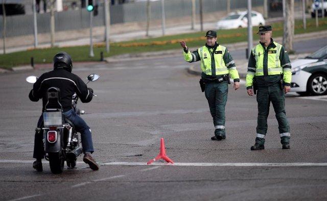 Dos guardias civiles de Tráfico paran a una moto que se encuentra cerca de la entrada del recinto de IFEMA (Madrid) durante la vigencia del Estado de Alarma
