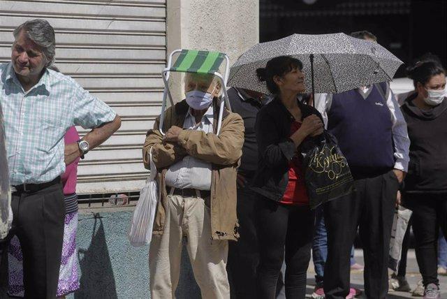 Personas hacen cola para poder acceder a una entidad bancaria en San Miguel de Tucumán, en el norte de Argentina, días después de que el Gobierno decretara la cuarentena para hacer frente al avance de la pandemia de Covid-19.