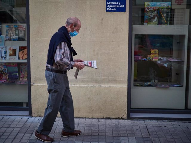 Un hombre camina con mascarilla leyendo un periódico durante el segundo día de la fase 0 de la desescalada y durante el periodo en el que la salida de mayores de 70 años se establece de 10 a 12 horas y de 19 a 20 horas, en Pamplona/Navarra (España) a 5