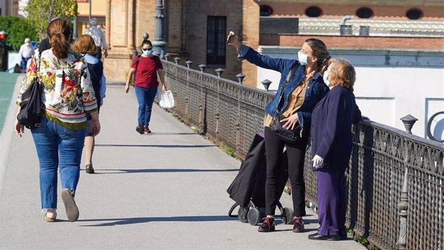 Personas mayor protegido con mascarilla pasea por el puente de Triana, foto de archivo
