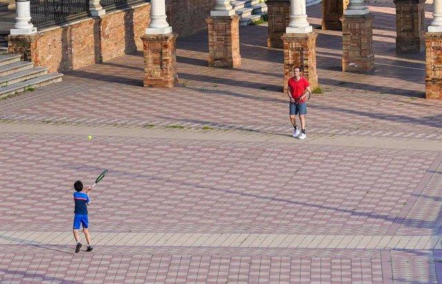 Un padre juega con su hijo al tenis en la Plaza de España un día después de que el Gobierno de España anunciara las medidas de desescalada por la pandemia del coronavirus, (Covid-19). Sevilla a 29 de abril del 2020