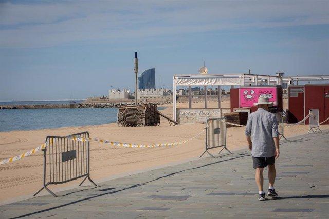 Un hombre pasa junto a la base náutica de la playa del Bogatell. En Barcelona (España), a 7 de mayo de 2020.