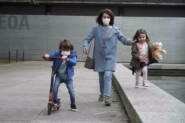 Una mujer pasea junto a una niña y un niño en las calles de Bilbao.