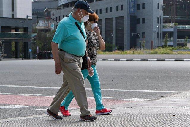 Dos personas protegidas con mascarilla pasean por la playa de la Malvarrosa durante su franja horaria permitida en la desescalada ante la crisis del Covid-19 en la que mayores de 14 años y menores de 69 tienen permitidas las salidas para pasear y hacer