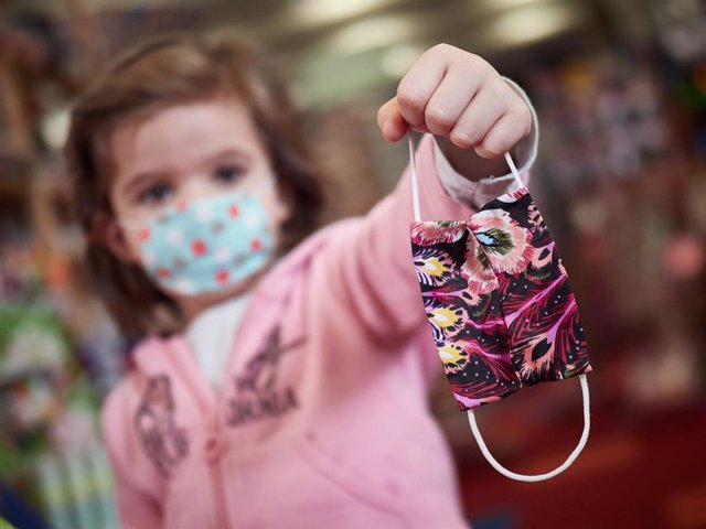 Una niña muestra una mascarilla infantil mientras sale a la calle en el primer día de relajamiento de las medidas de confinamiento marcadas por el Gobierno de España durante el Estado de Alarma.